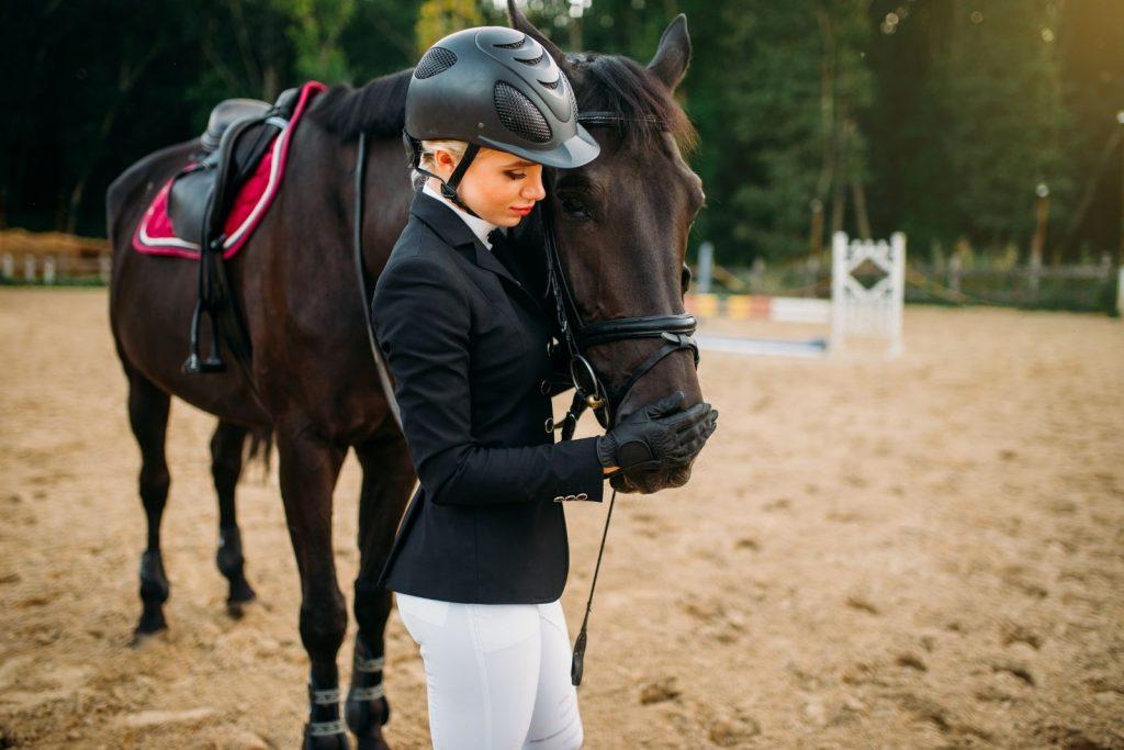 a beautiful woman petting her horse