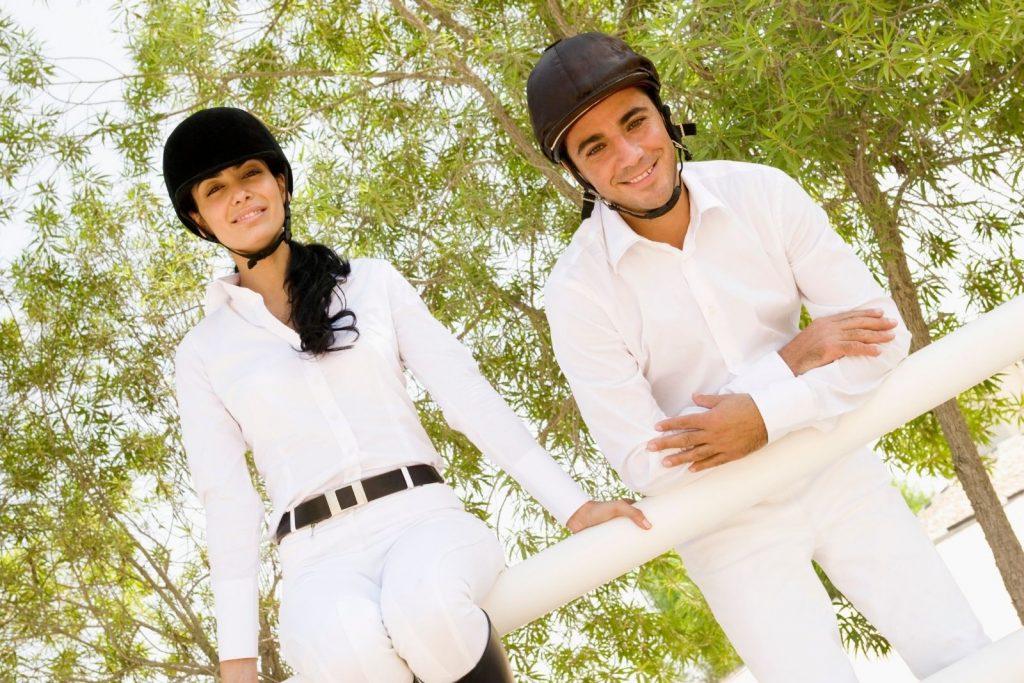 equestrians wearing horse riding helmets
