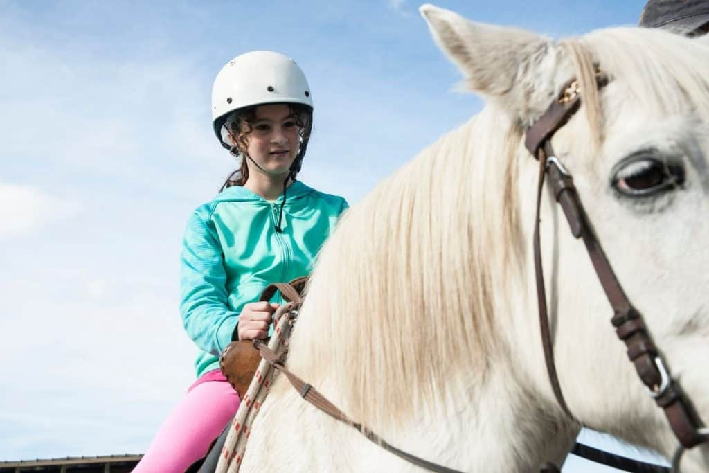 young girl riding a white horse